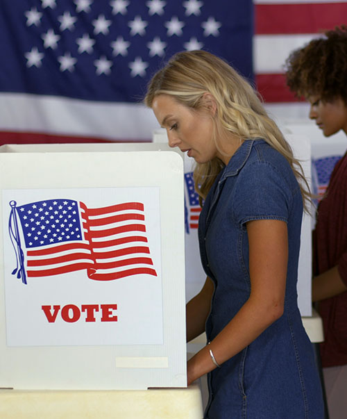 A caucasian woman and African American woman voting at the polling station.